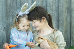 Mother and her child holding cute scarlet Easter rabbit Royalty Free Stock Image