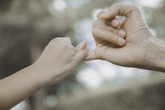 Mother and her child hooking their fingers to make a promise. Vintage style Royalty Free Stock Photo