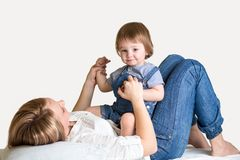 Mother and her child lying on the bed and smiling Royalty Free Stock Images