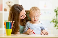 Mother and her child pencil together Stock Photography