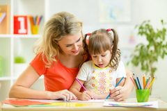 Mother and her child pencil together Stock Photos