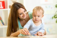 Mother and her child play with colorful puzzle toy Stock Images