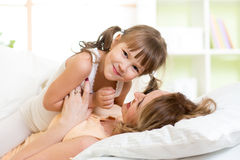 Mother and her child play and laugh in bed Stock Photos