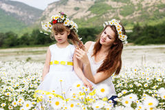 Mother with her child playing in camomile field Royalty Free Stock Photos