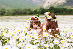 Mother with her child playing in camomile field Stock Images