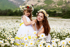 Mother with her child playing in camomile field Royalty Free Stock Photography