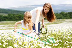 Mother with her child playing in camomile field Stock Photo