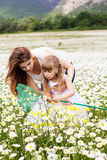 Mother with her child playing in camomile field Royalty Free Stock Photo