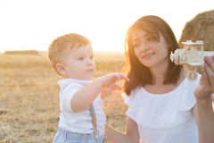 Mother and her child playing in field with toy airplane. Stock Images