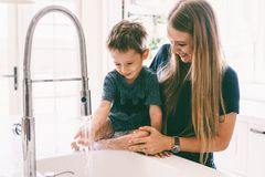 Mother with her child playing in kitchen sink stock photography