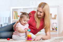 Mother with her child playing with wooden blocks stock images