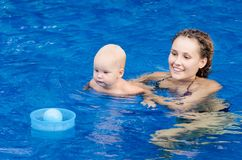 Mother and her child in the pool. Woman playing with a ball with his little daughter. Royalty Free Stock Images