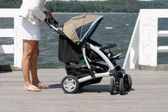 Mother with her child in stroller walking Stock Photos