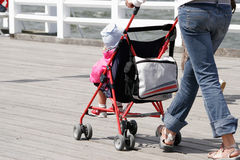 Mother with her child in stroller walking Stock Photo