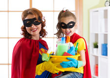 Mother and her child in Superhero costume. Mum and kid ready to house cleaning. Houseworking and housekeeping. Royalty Free Stock Photo