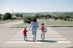 Mother and her children crossing road Stock Photos