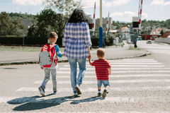 Mother and her children crossing road Stock Photography