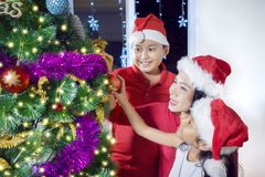 Mother and her children decorating Christmas tree Royalty Free Stock Photo
