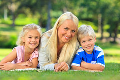Mother with her children lying down in the park Royalty Free Stock Image