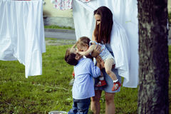 Mother with her children outside hanging laundry, brother playing with little sister, happy loving family Stock Photo