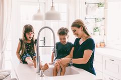 Mother with her children playing in kitchen sink royalty free stock photography