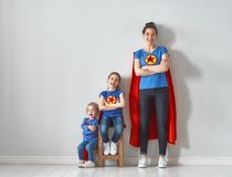 Family in Superhero costumes. Mother and her children playing together. Girls and mom in Superhero costumes. Mum and kids having fun and smiling. Family holiday stock image