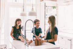 Mother with her children playing in kitchen sink royalty free stock images