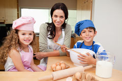 Mother and her children preparing cake Royalty Free Stock Photo