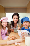 Mother and her children preparing dough Stock Image