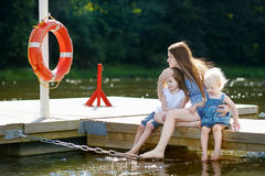 Mother and her children sitting on a wooden pier Royalty Free Stock Images