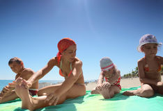 Mother and her children, son and daughters. Mother and her children, son and two daughters, sitting on the green coverlet on a sandy beach and doing gymnastics Royalty Free Stock Photo