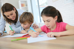Mother with her children spending time together drawing Royalty Free Stock Photos