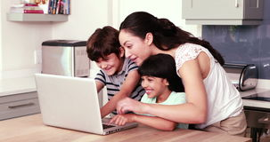Mother and her children using laptop. At home stock video footage