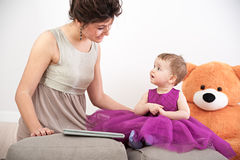 Mother and her curious daughter in violet dress with teddy bear Stock Images