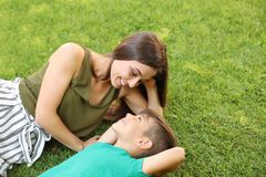 Mother with her cute child on green grass in park royalty free stock images