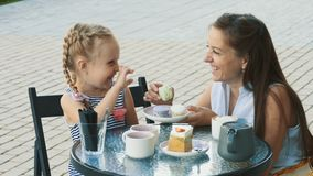 Mother and her cute little daughter in outdoor cafe. Beautiful brunette mother and her cute little daughter sitting in outdoor summer cafe. Happy family drinks stock footage