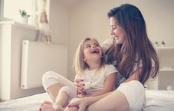 Mother with her cute little daughter sitting on bed. stock photos