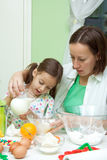 Mother and her daughter, bakeing in the kitchen Stock Photo