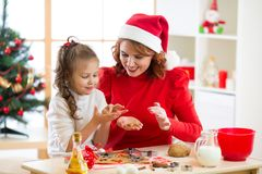 Mother and daughter baking Christmas cookies at decorated tree. Mom and child bake Xmas sweets. Family with kids royalty free stock image