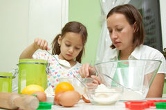 Mother and her daughter, baking in the kitchen Royalty Free Stock Photos