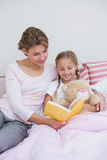 Mother with her daughter at bedtime Stock Photo