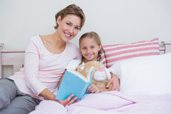 Mother with her daughter at bedtime Stock Images