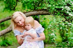 Mother and her daughter in blooming garden Stock Image