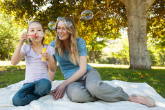 Mother with her daughter blowing soap bubbles at park Stock Image