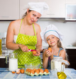 Mother and her daughter in cap cooking omelette Stock Photos