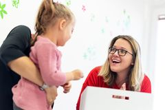 Mother and her daughter in child occupational therapy session doing sensory playful exercises with the child therapist. royalty free stock photos