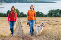 Mother and her daughter with dog walking outdoors Royalty Free Stock Image