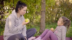 Mother and her daughter eating apples stock video footage