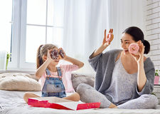 Mother and her daughter eating donuts Stock Images