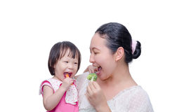 Mother and her daughter eating vegetables Stock Images